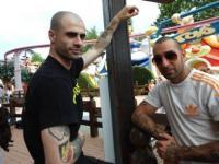 Luigi ist rechts auf dem Bild; am rechten Oberarm der Person links ist eine SS-Tätowierung zu erkennen auf schwarz-weiß-rotem Hintergrund