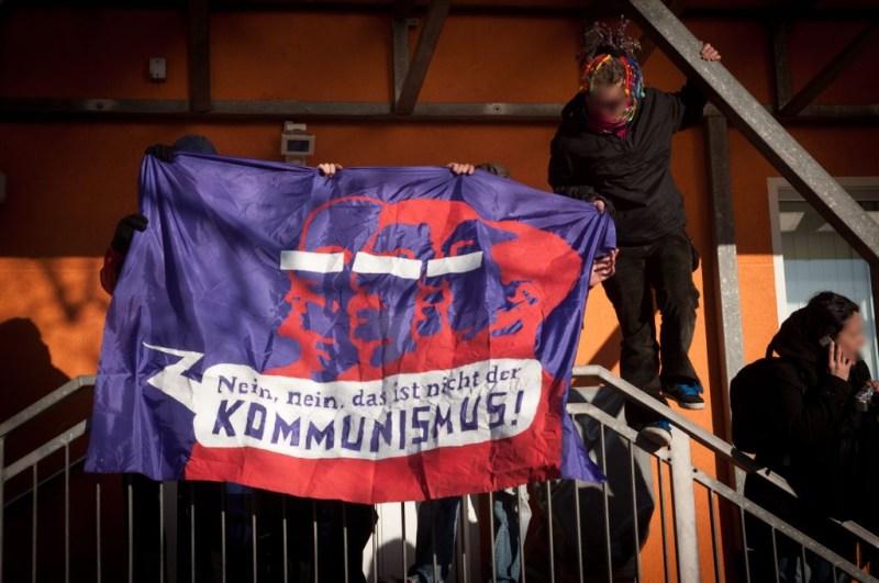 Stalin-Kritiker*innen halten Transpi mit dem Slogan