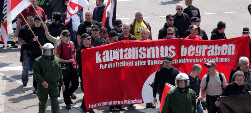 "Baumann im roten T-Shirt links neben dem Transparent als ""Nationaler Sanitäter"" am 1. Mai 2009 in Ulm"