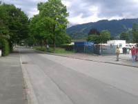 Einfahrt auf den Parkplatz (mit Bürgerspitzeln und Mordmaschine für das Kapital)